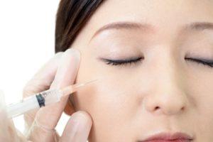 目の下に美容注射を受ける女性